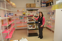 Staying stocked: Medical case manager Katie Roders stands in the Francis House pantry. The organization relies on community donations to keep the shelves stocked all year long. Photo by Bruce Hardin