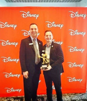 Zebra Foundation for Youth Board Chairman Scott Bowman and Zebra Coalition Director Dexter Foxworth receive a 2015 Disney grant.